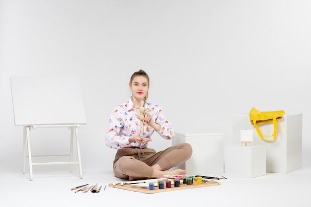 Вид спереди молодая женщина держит игрушечную человеческую фигуру на белом фоне