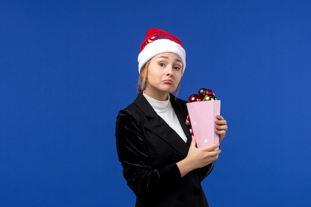 Front view young female holding tree toys on blue background new year holiday emotion color