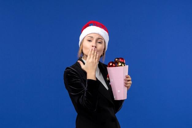 Vista frontale la giovane femmina che tiene i giocattoli dell'albero sul colore blu delle emozioni di festa del nuovo anno del fondo