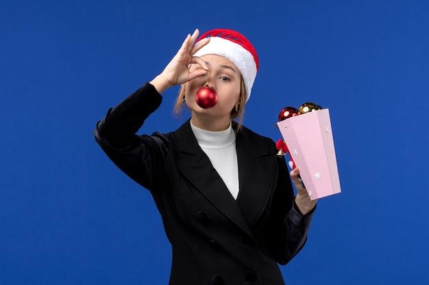 파란색 배경에 파란색 감정 새 해 휴일에 나무 장난감을 들고 전면보기 젊은 여성