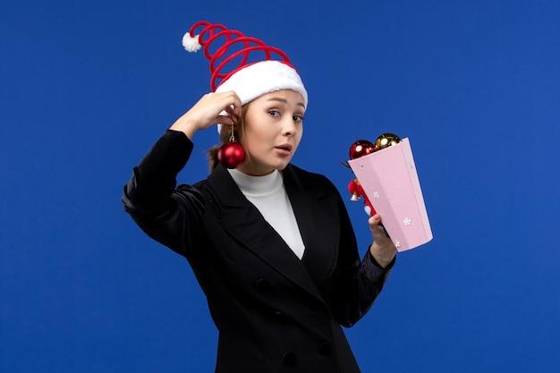 Вид спереди молодая женщина, держащая елочные игрушки на синем столе, синяя эмоция, новогодний праздник