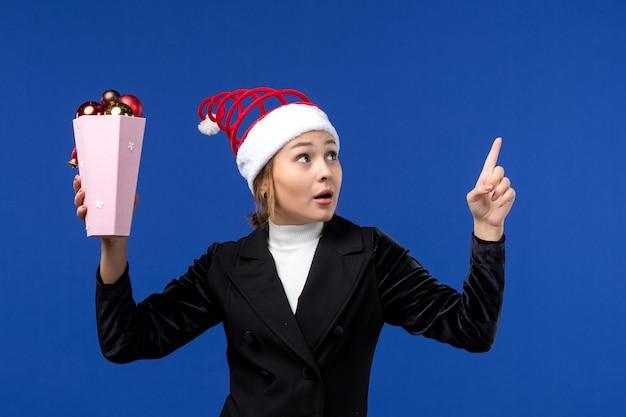 正面図水色の壁に木のおもちゃを保持している若い女性新年の休日の女性青