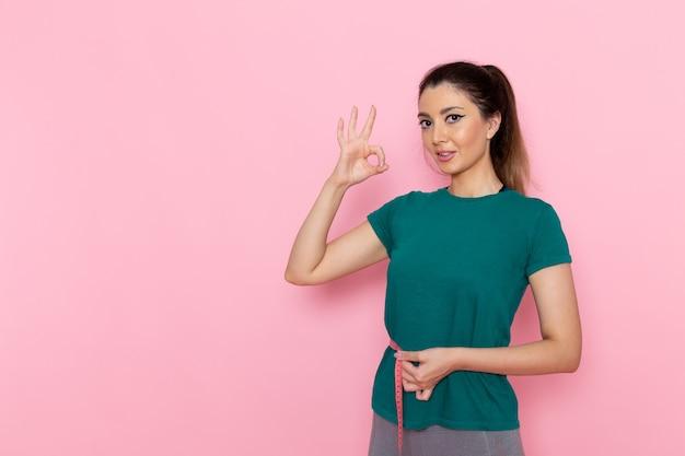분홍색 벽 아름다움 스포츠 운동 선수 운동 슬림에 허리 측정을 들고 전면보기 젊은 여성