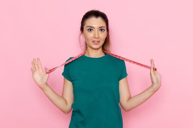 밝은 분홍색 벽 아름다움 스포츠 운동 선수 운동 슬림에 허리 측정을 들고 전면보기 젊은 여성