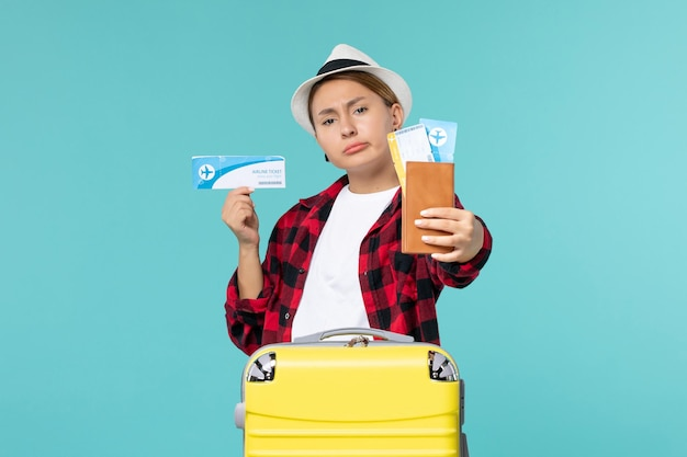 Вид спереди молодая женщина, держащая бумажник и билет на синем пространстве