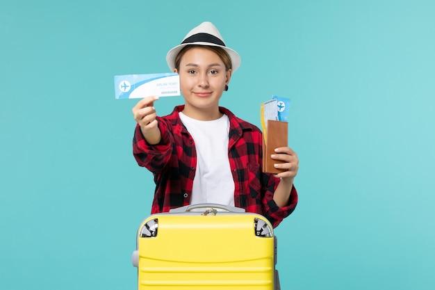 푸른 공간에 지갑과 티켓을 들고 전면보기 젊은 여성