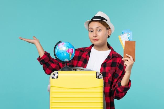 青い机の上のチケットと財布を保持している若い女性の正面図