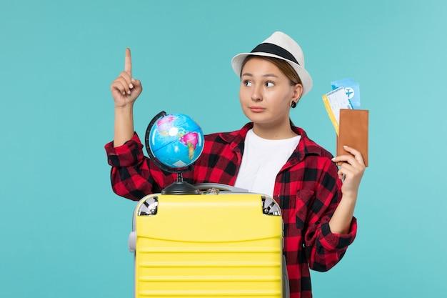 Вид спереди молодая женщина, держащая бумажник с билетами на синем полу, путешествие, отпуск, путешествие, женщина