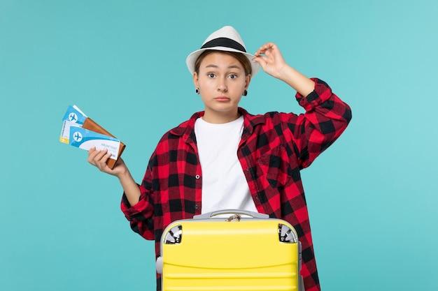 青いスペースにチケットと財布を保持している若い女性の正面図