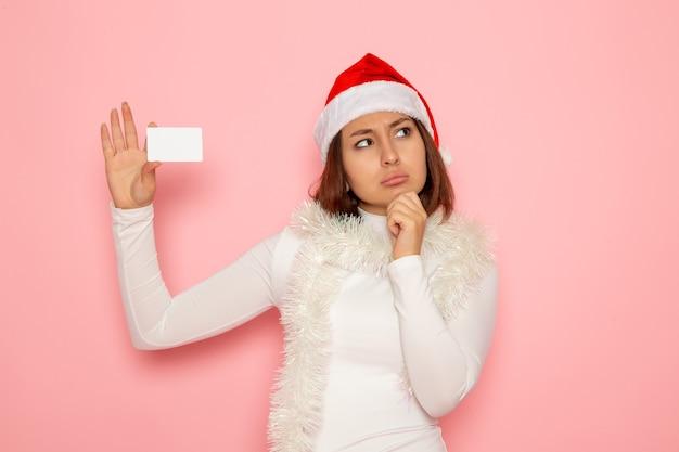 핑크 벽 크리스마스 휴일 새 해 패션 컬러 돈에 흰색 은행 카드를 들고 전면보기 젊은 여성