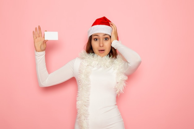 분홍색 벽 크리스마스 휴일 새 해 색 돈에 흰색 은행 카드를 들고 전면보기 젊은 여성