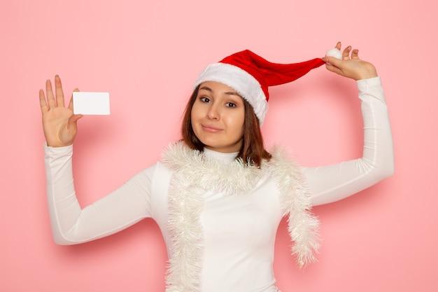 핑크 벽 크리스마스 휴일 새 해 패션 색상 돈에 흰색 은행 카드를 들고 전면보기 젊은 여성