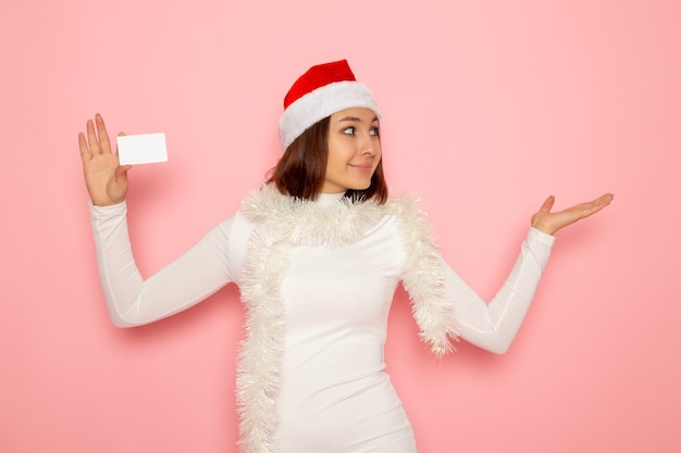 분홍색 벽 크리스마스 새 해 색상 돈 휴가에 흰색 은행 카드를 들고 전면보기 젊은 여성