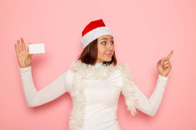 Front view young female holding white bank card on pink wall christmas new year fashion color money holiday