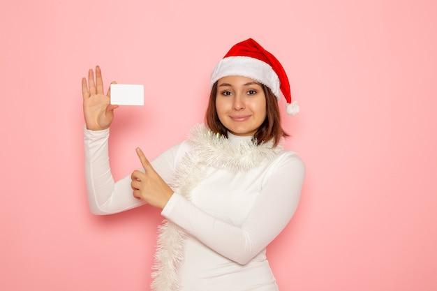 Vista frontale giovane femmina che tiene carta bancaria bianca sulla parete rosa natale capodanno moda colore soldi vacanza
