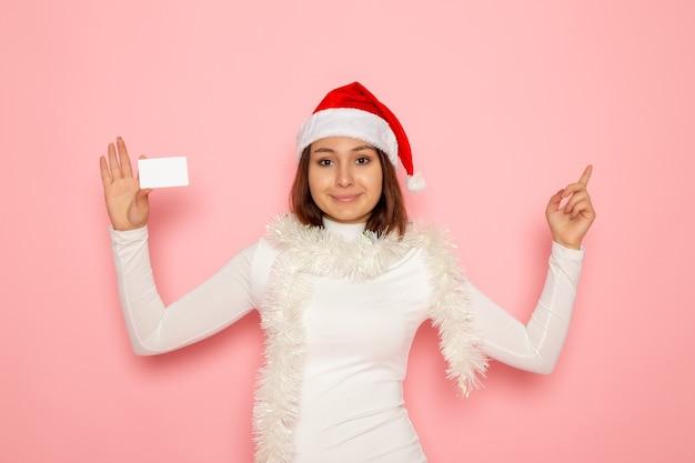 Vista frontale giovane femmina che tiene carta bancaria bianca sulla parete rosa natale capodanno moda colore soldi vacanze