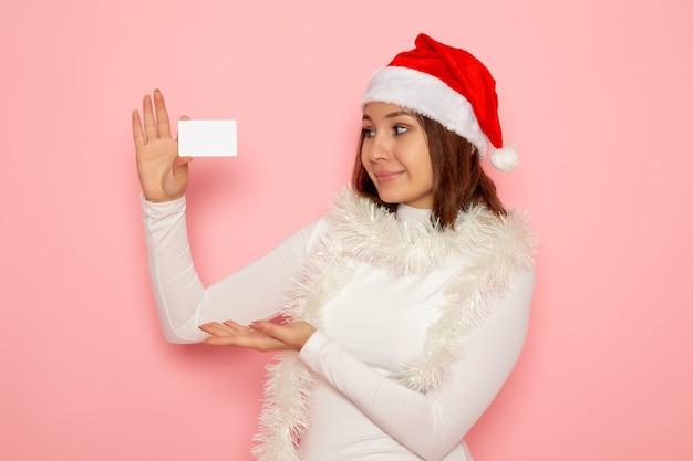 Vista frontale giovane femmina in possesso di carta di credito bianca sulla parete rosa natale capodanno moda soldi vacanza