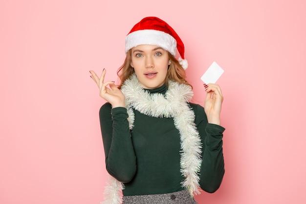 Vista frontale giovane femmina che tiene carta bancaria bianca sul muro rosa modello emozione vacanza natale capodanno