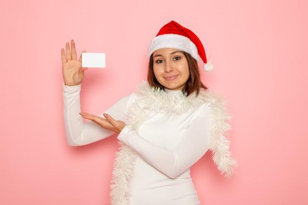 Vista frontale giovane femmina che tiene carta bancaria bianca sulla parete rosa nuovo anno moda colore soldi vacanza
