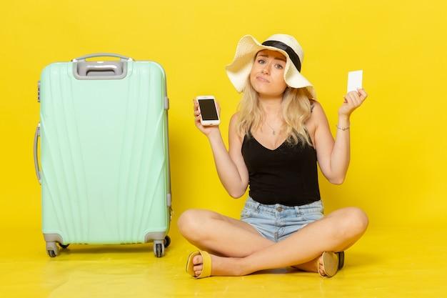 白いカードと電話を保持している正面図若い女性
