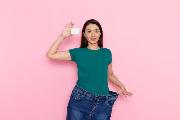ピンクの壁に白いカードを保持している正面図若い女性運動スポーツトレーニングアスリート腰の美しさ
