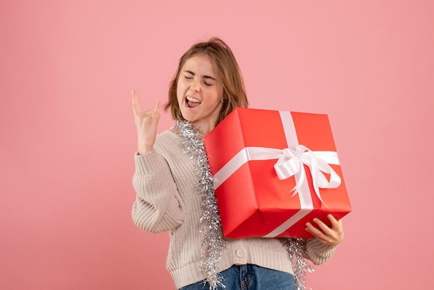 Вид спереди молодая женщина, держащая рождественский подарок