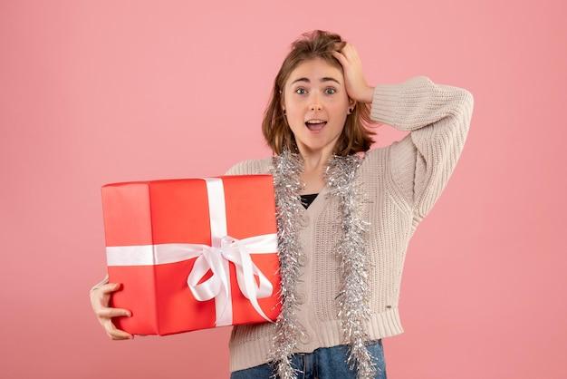 クリスマスプレゼントを保持している正面図若い女性