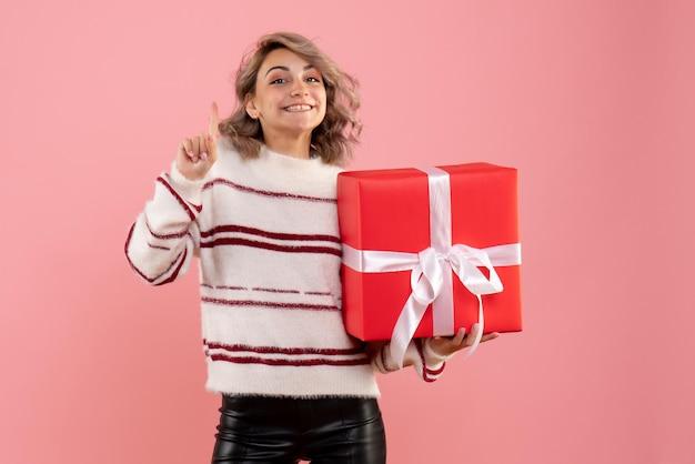 Giovane femmina di vista frontale che tiene regalo di natale