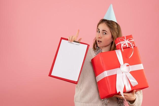 크리스마스 선물 및 메모를 들고 전면보기 젊은 여성