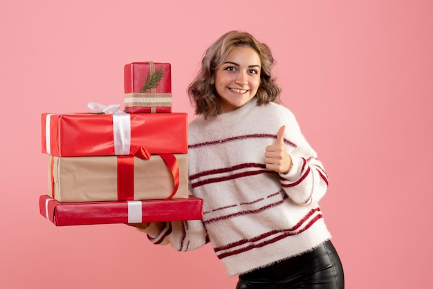 Front view young female holding xmas presents
