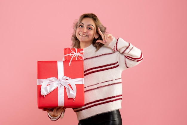 Front view young female holding xmas presents Free Photo