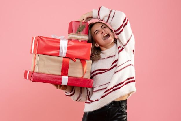 Giovane femmina di vista frontale che tiene i regali di natale