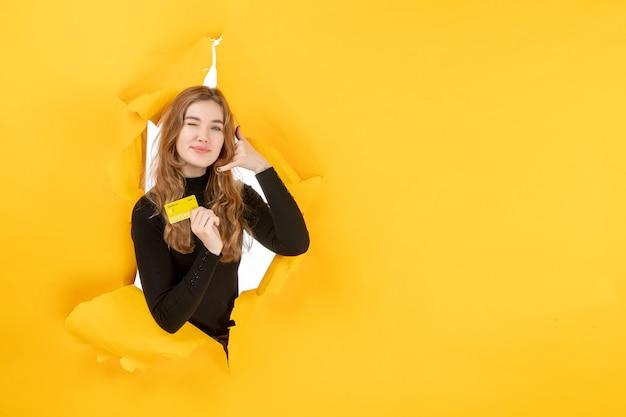 Вид спереди молодая женщина держит желтую банковскую карту на желтой стене