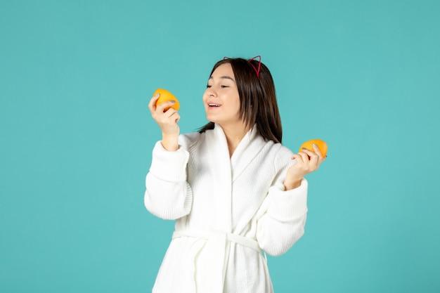 青い背景にオレンジスライスを保持しているバスローブの正面図若い女性