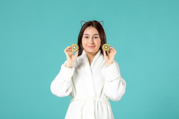 青い背景にスライスしたキウイを保持しているバスローブの正面図若い女性 無料写真
