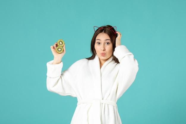 青い背景にスライスしたキウイを保持しているバスローブの正面図若い女性