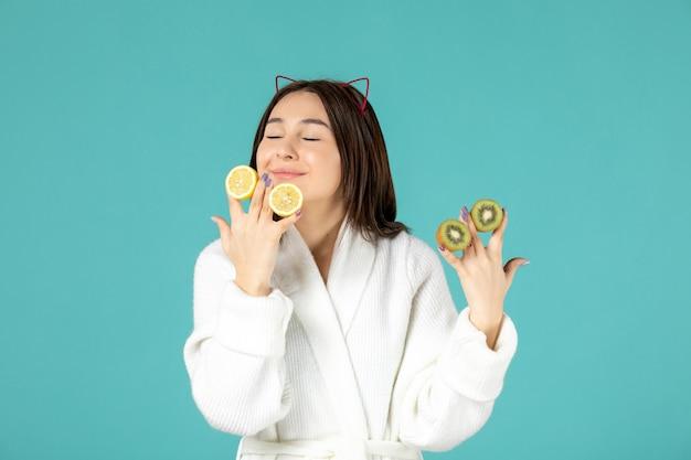青い背景にスライスしたレモンとキウイを保持しているバスローブの正面図若い女性
