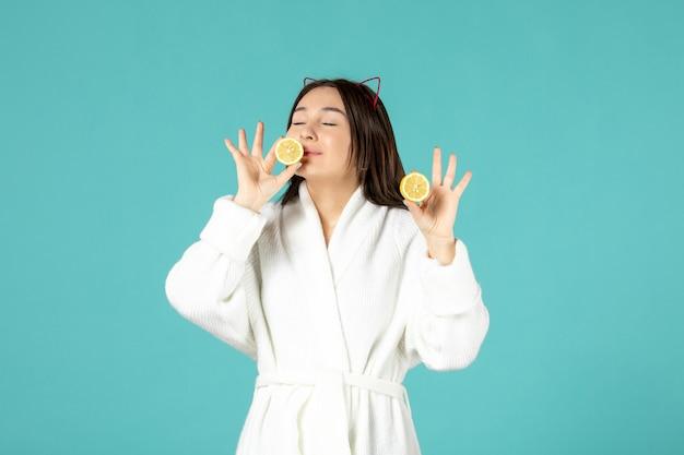 파란색 배경에 얇게 썬 레몬을 들고 목욕 가운을 입은 젊은 여성