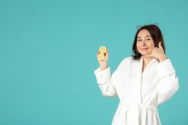 青い背景にスライスしたレモンを保持しているバスローブの正面図若い女性