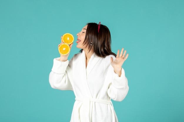 青い背景にスライスしたオレンジ色のバスローブを着た若い女性の正面図 無料写真