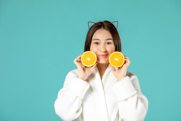 青い背景にスライスしたオレンジ色のバスローブを着た若い女性の正面図