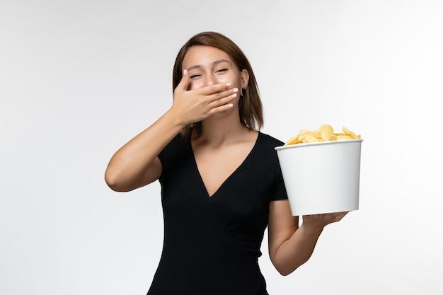 Вид спереди молодая женщина в черной рубашке держит картофельные чипсы и смеется на белой поверхности