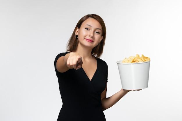 Вид спереди молодая женщина в черной рубашке держит картофельные чипсы и улыбается на белой поверхности