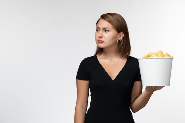 Вид спереди молодая женщина в черной рубашке, держащая картофельные чипсы на белой поверхности