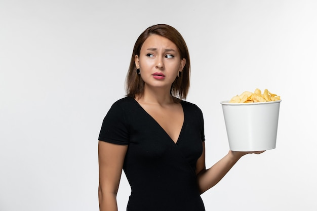 Вид спереди молодая женщина в черной рубашке, держащая картофельные чипсы на белом столе