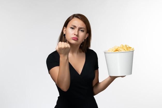 Вид спереди молодая женщина в черной рубашке держит картофельные чипсы, показывая кулак на белой поверхности