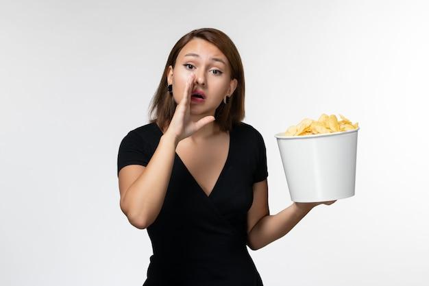 Вид спереди молодая женщина в черной рубашке держит картофельные чипсы, шепчет на белой поверхности