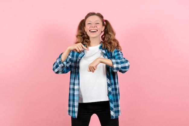 파란색 체크무늬 셔츠를 입은 젊은 여성이 분홍색 벽에 손목을 가리키는 어린 소녀 청소년 감정 모델 여성 색상