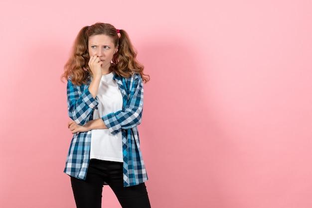 正面図ピンクの背景にポーズをとって考えている青い市松模様のシャツの若い女性子供の女の子の若者の感情モデルファッション