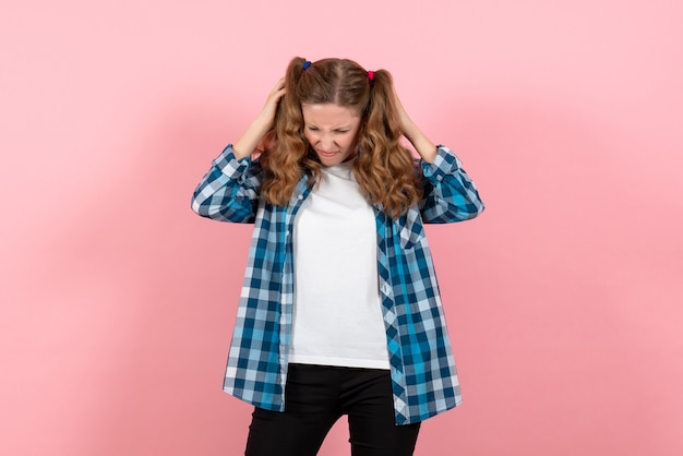 ピンクの背景にポーズをとる青い市松模様のシャツの正面図若い女性子供の女の子の若者の感情モデルファッション